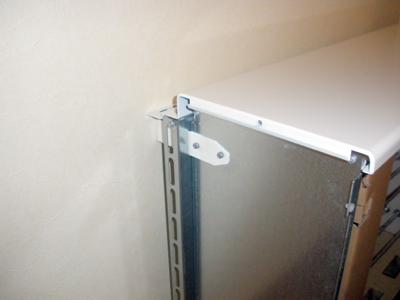 転倒防止金具と蓄熱式暖房器本体を固定